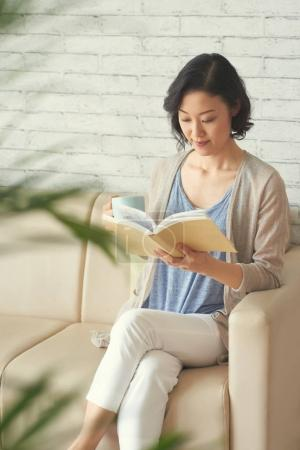 Asian young woman drinking tea and enjoying a book