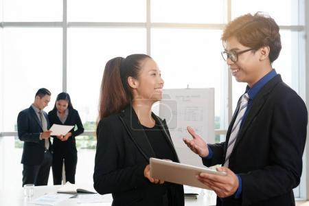 Photo for Asian young coworkers working on project with help of digital tablet - Royalty Free Image