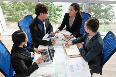 High angle view of confident Vietnamese business people wrapped up in work while sitting at table in spacious boardroom with panoramic windows