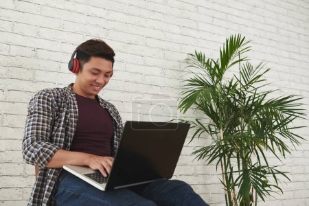 Smiling Asian young man working on laptop