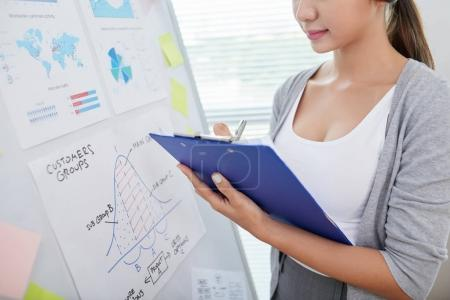 Cropped image of business woman analyzing various charts and graphs and taking notes