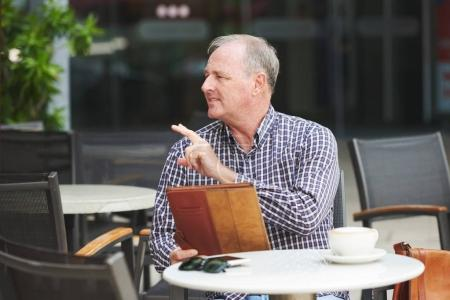 Senior man in outdoor cafe calling for waiter