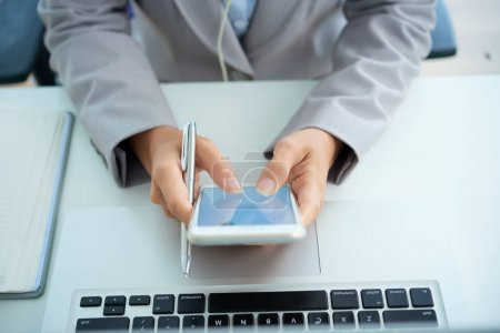 Close-up image of business woman using application on her smartphone