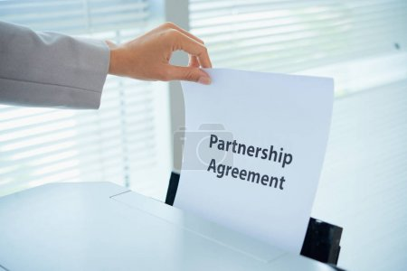 Hand of female entrepreneur printing out partnership agreement
