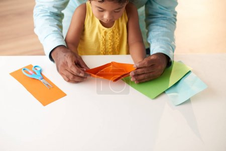 little Indian girl sitting on laps of her father and holding handmade paper ship in hands