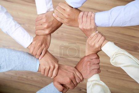 Collaborateurs, tenant les poignets des uns des autres: ensemble nous sommes plus forts