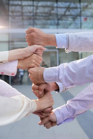 Clenched fists of business people in high tower: teamwork concept