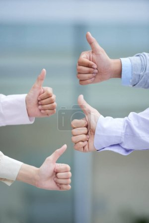 Photo for Business team members showing thumbs-up as symbol of approval - Royalty Free Image