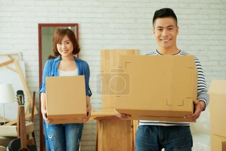 Photo for Smiling asian young Couple carrying carton boxes while house moving - Royalty Free Image