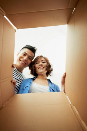 asian couple looking inside of carton box
