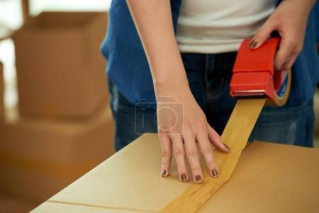 Photo for Partial view of woman packing stuff in carton box and using Scotch tape for moving - Royalty Free Image