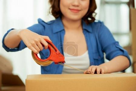 Photo for Woman packing stuff in carton box with Scotch tape for moving - Royalty Free Image