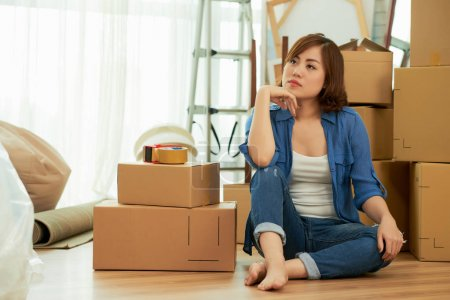 thinking beautiful young asian woman sitting on floor in room with carton boxes