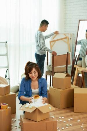 Photo pour Asiatique couple emballage leur trucs wile maison déplacer - image libre de droit