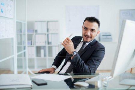 Photo pour Bel homme d'affaires réussi en costume assis à la table avec écran d'ordinateur dans le bureau - image libre de droit