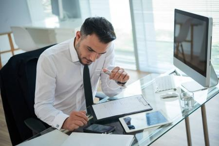Foto de Hombre de negocios leyendo el mensaje en el teléfono móvil mientras está sentado en la mesa con el ordenador - Imagen libre de derechos