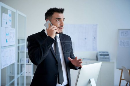 businessman in suit talking on mobile phone while standing in office