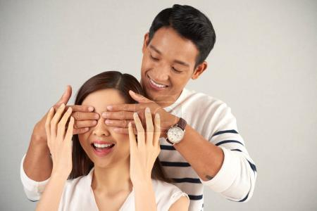 handsome Asian man standing behind young woman and covering her eyes with hands, studio shot