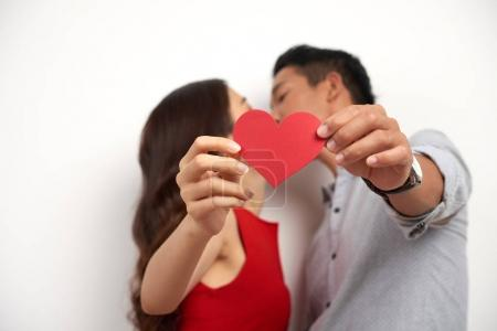 Profile view of affectionate Asian couple kissing while standing against white background and showing Saint Valentines card to camera, studio shot