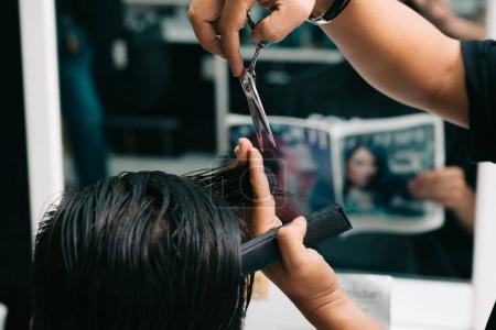 Close-up image of barber cutting piece of hair