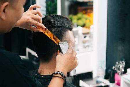 Close-up image of barber using trimmer when doing stylish haircut for a young man