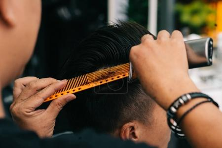 Close-up image of hairdresser using special comb to trim every piece of hair that is too long