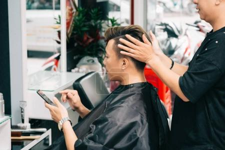 Barber making final touches on haircut of male client