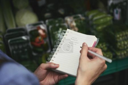 Close-up image of woman checking her shopping list