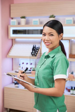 Cosmetics shop managers checking assortment and taking notes