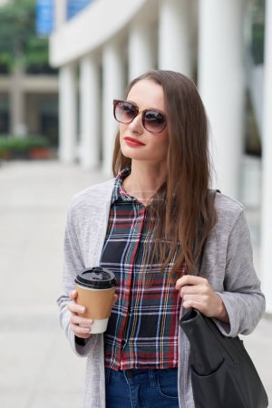 Young woman in sunglasses drinking take-out coffee on the way to work