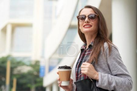 Young business woman with take out coffee hurrying to work