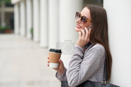 Cheerful young woman with take-out coffee talking on the phone