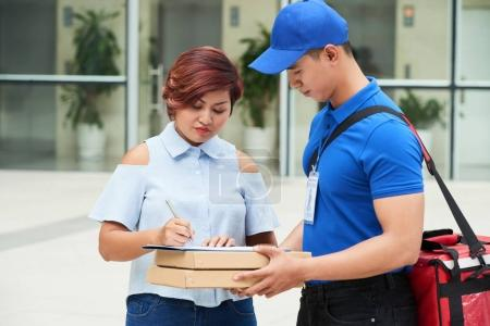 Vietnamese young woman having her food delivered to office