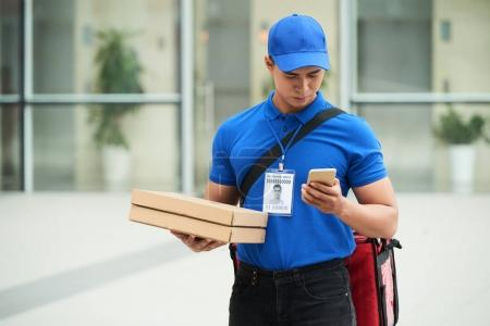Delivery man with two pizzas checking address in his smartphone