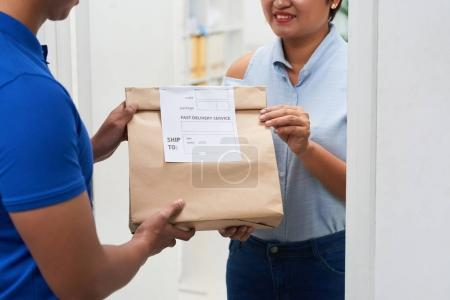 Delivery man giving package to happy woman