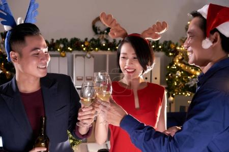 Coworkers cheering with wine glasses at office party