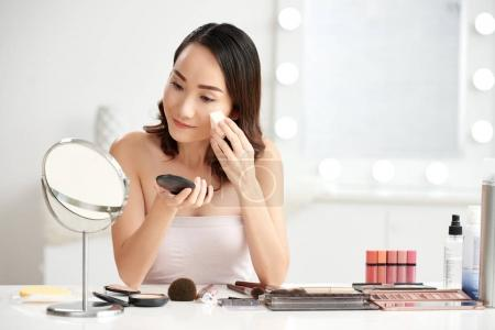 Pretty Chinese woman applying powder foundation on her face