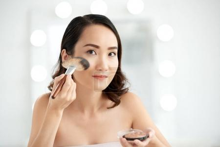 Pretty woman applying highlighter on highest points of her cheeks