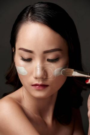 Beautiful Asian woman applying face mask with synthetic brush