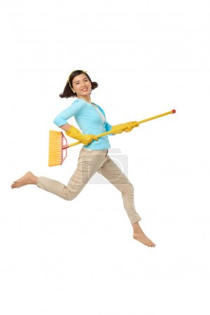 Energetic Asian woman wearing rubber gloves and jumping in air with broom, isolated on white background