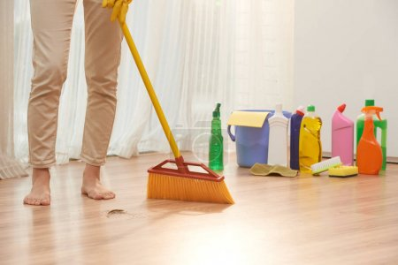 barefoot woman sweeping floor with broom while wrapped up in housecleaning