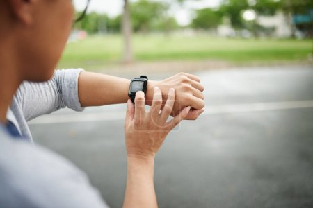 Hands of man checking heart rate on smart watch