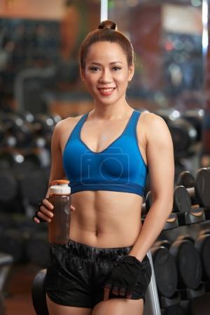 Attractive Vietnamese sportswoman drinking water after training
