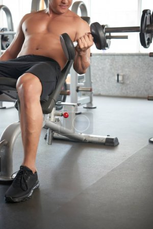 Cropped image of fit man exercising in gym