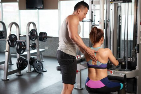 Rear view of fitness trainer helping female client to perform exercise