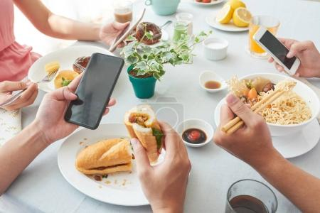 Group of people eating and checking smartphones
