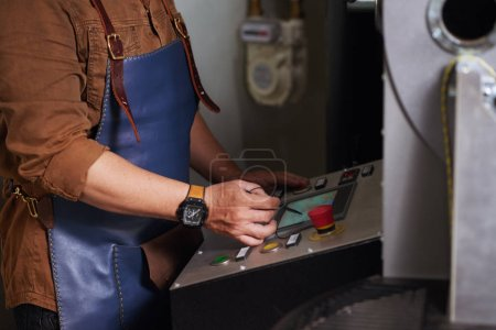 Close-up image of worker using modern coffee roaster