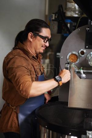 Smiling owner in glasses checking roasting coffee beans