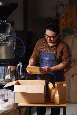 Smiling owner putting packed coffee into cardboard box