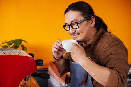 Smiling Asian man smelling coffee he made with his new espresso machine